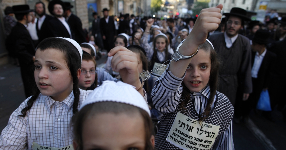 Ultra-Orthodox Jewish children wear handcuffs as they protest against a uniform draft law to replace the Tal Law on July 16, 2012, in Jerusalem, Israel. The Tal Law, which exempts ultra-Orthodox yeshiva students from mandatory military service, was declared unconstitutional by the High Court in February, and is due to expire in August.</p>