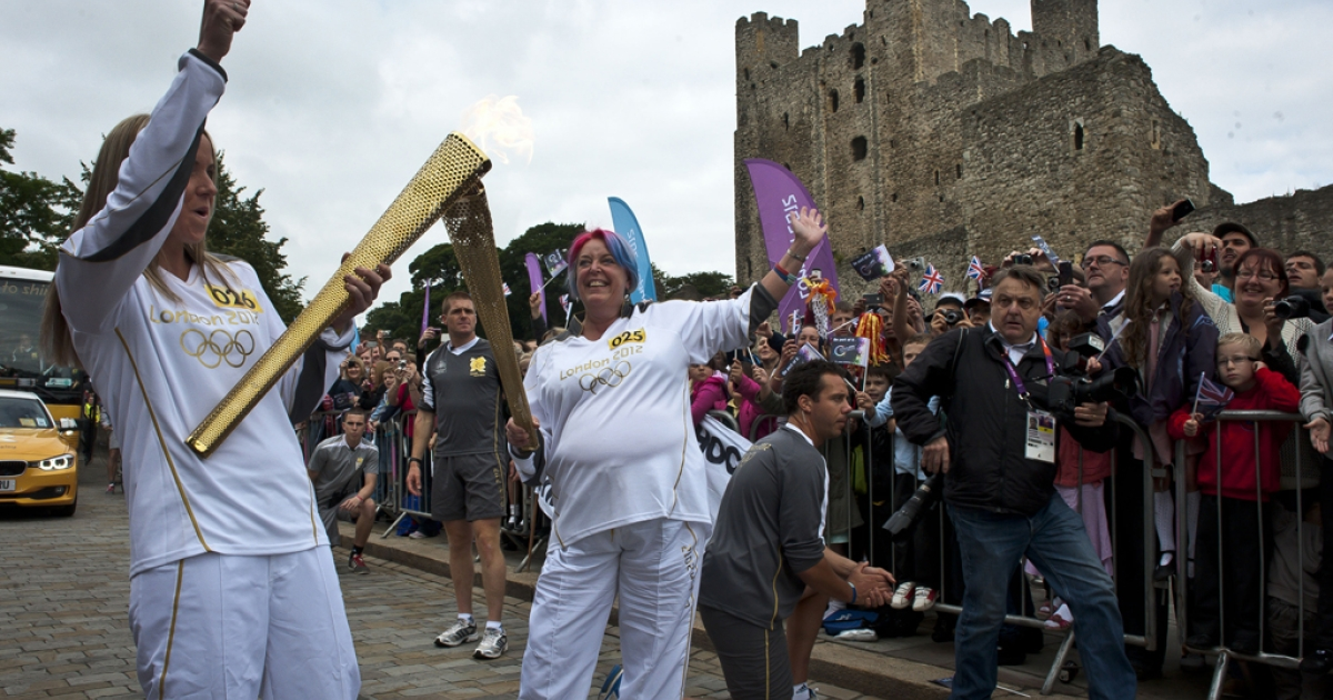 Torchbearer Jessica Cheesman passes the Olympic flame to Sarah Mooney outside of Rochester Castle during Day 63 of the London 2012 Olympic Torch Relay on July 20, 2012 in Rochester, England. The Olympic flame is now on day 63 of a 70-day relay involving 8,000 torchbearers covering 8,000 miles.</p>