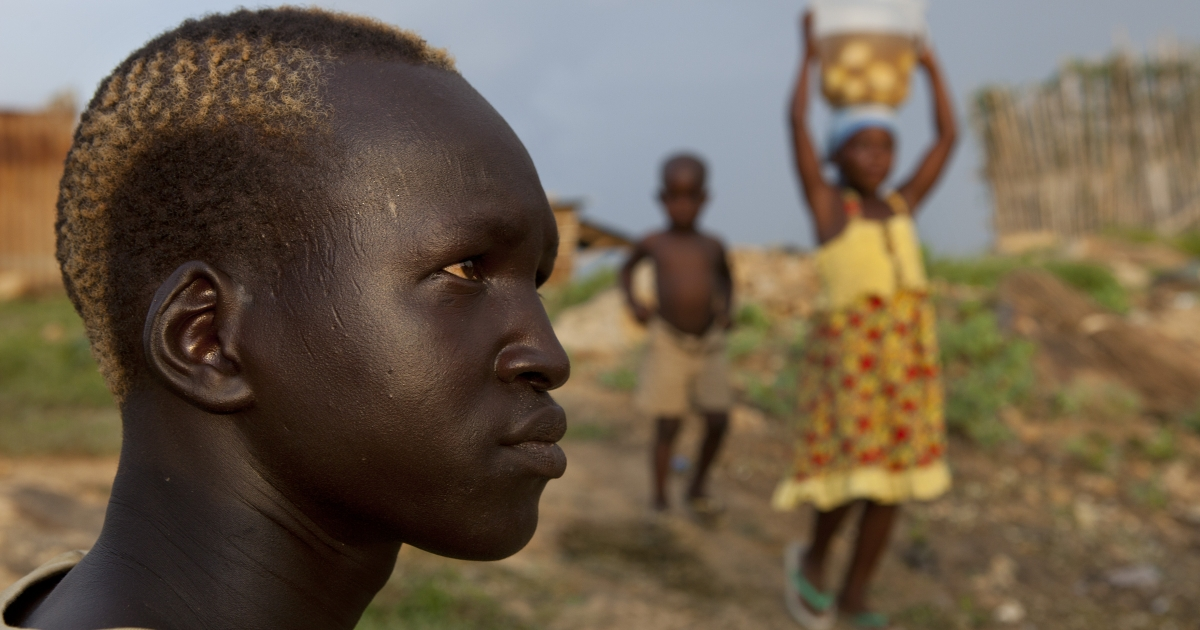 A Sudanese man sits outside his home as children carry food to cook, on July 20, 2012 in Juba, South Sudan. After breaking away from Sudan last year, South Sudan recently celebrated its first independence anniversary. Over the past year repeated conflict including corruption scandals and economic difficulties have plagued the new country.</p>