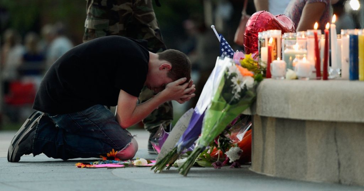 Mourners pray in front of a makeshift memorial at the Aurora Municipal Center.</p>