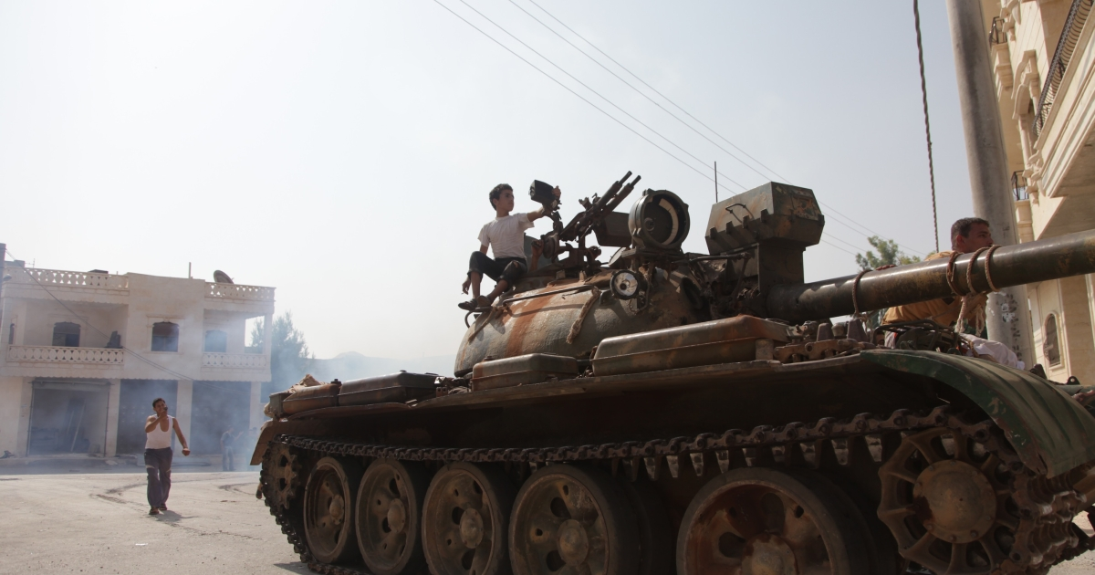 Syrian rebel fighters celebrate on top of a tank captured from the Syrian government forces at a checkpoint in the village of Anadan, about five kilometres (3.8 miles) northwest of Aleppo, on July 30 2012, after a 10-hour battle.</p>
