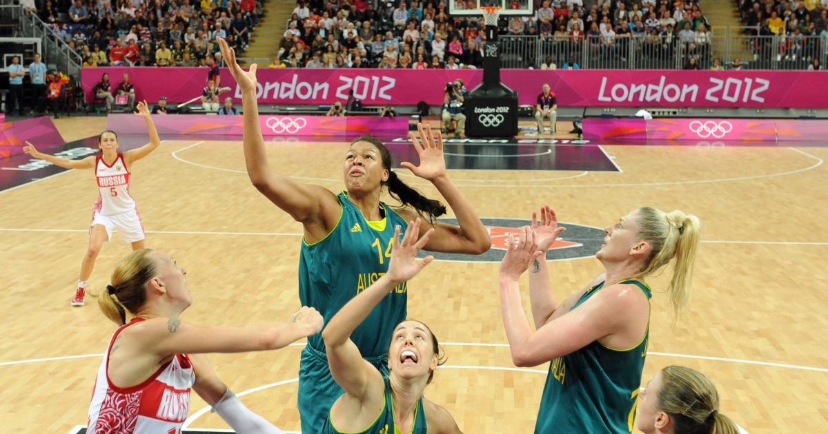 Australian center Elizabeth Cambage (C) vies with Russian centre Irina Osipova (L) with Liz Jackson (top R) standing by during the women's preliminary round group A basketball match of the London 2012 Olympic Games Russia vs. Australia on August 3, 2012 at the basketball arena in London.</p>