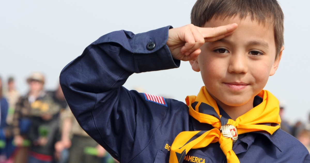 A US boy scout salutes during a World War II commemoration on April 16, 2011.</p>
