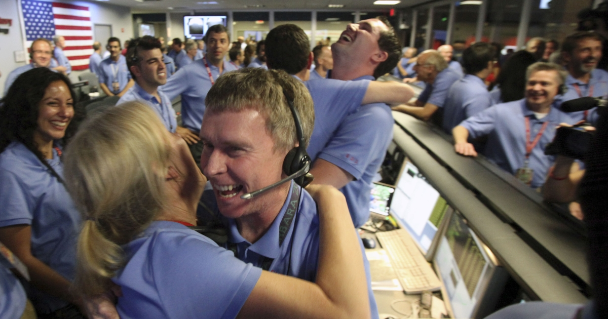 Telecom engineer Peter Ilott hugs a colleague, celebrating a successful landing inside the Spaceflight Operations Facility for NASA's Mars Science Laboratory Curiosity rover at Jet Propulsion Laboratory on August 5, 2012 in Pasadena, California.</p>