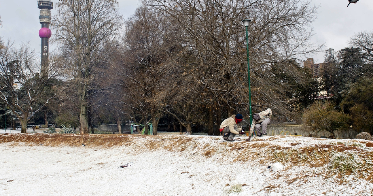 Two people play with snow in a park on August 7, 2012 in Johannesburg. Snow falls annually in the mountains of South Africa and Lesotho, which even hosts a ski resort. But some high-altitude border posts between the countries received so much snow today that they were forced to close.</p>
