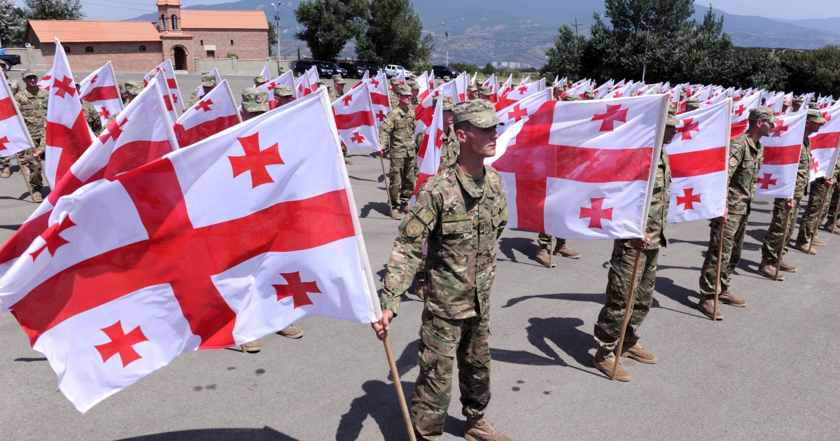 Georgian soldiers hold national flags at a memorial cemetry in Tbilisi on August 8, 2012, as Georgians mark the anniversary of the Ossetian conflict.</p>