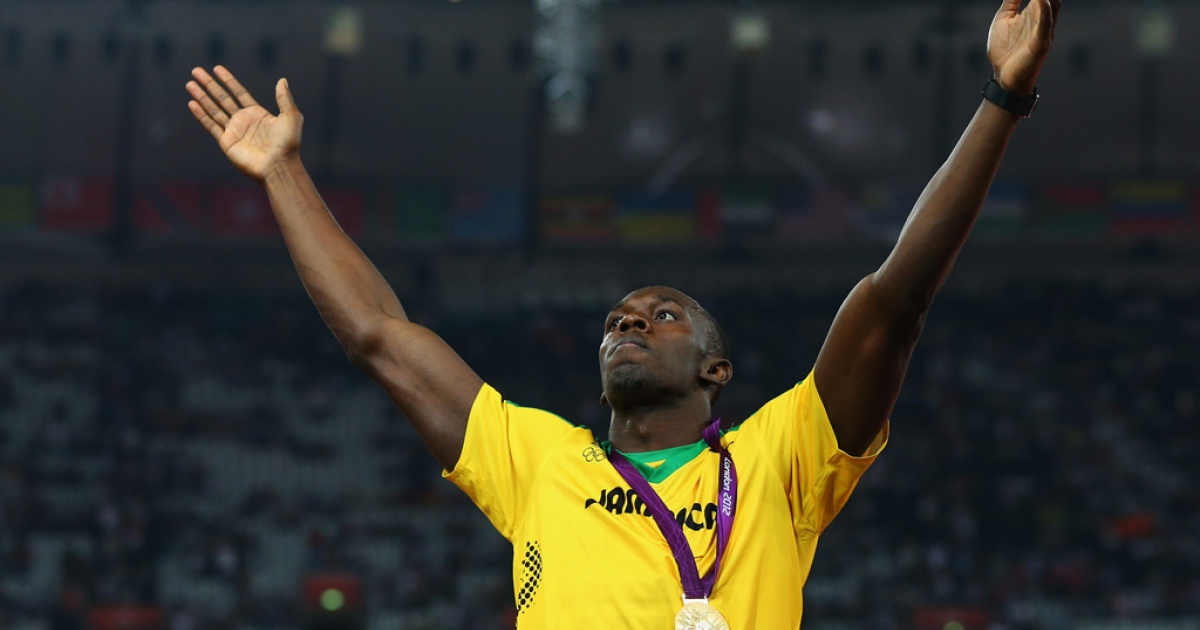 Gold medalist Usain Bolt of Jamaica celebrates on the podium during the medal ceremony for the men's 200m at the London 2012 Olympic Games on August 9, 2012 in England.</p>
