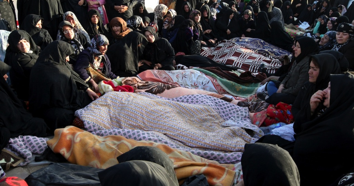 Iranians mourn over the covered bodies of loved ones in the village Baje-Baj, near the town of Varzaqan, on August 12, 2012.</p>