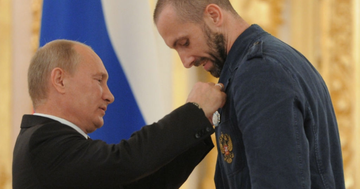 Russian President Vladimir Putin gives volleyball player Sergey Tetyukhin a state honor in Moscow on August 15, 2012.</p>