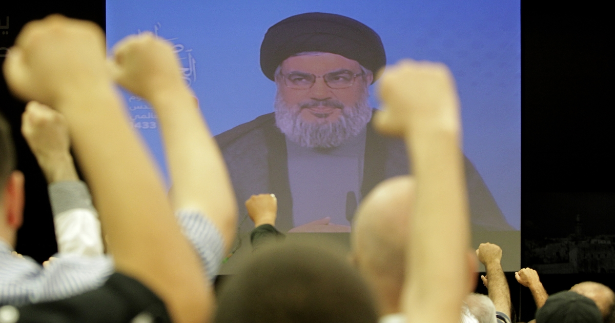 Lebanese Shiite men raise their fists up as they listen to a speech via videolink by Hezbollah leader Hassan Nasrallah marking Al-Quds (Jerusalem) Day in the southern suburbs of Beirut on August 17, 2012 .</p>