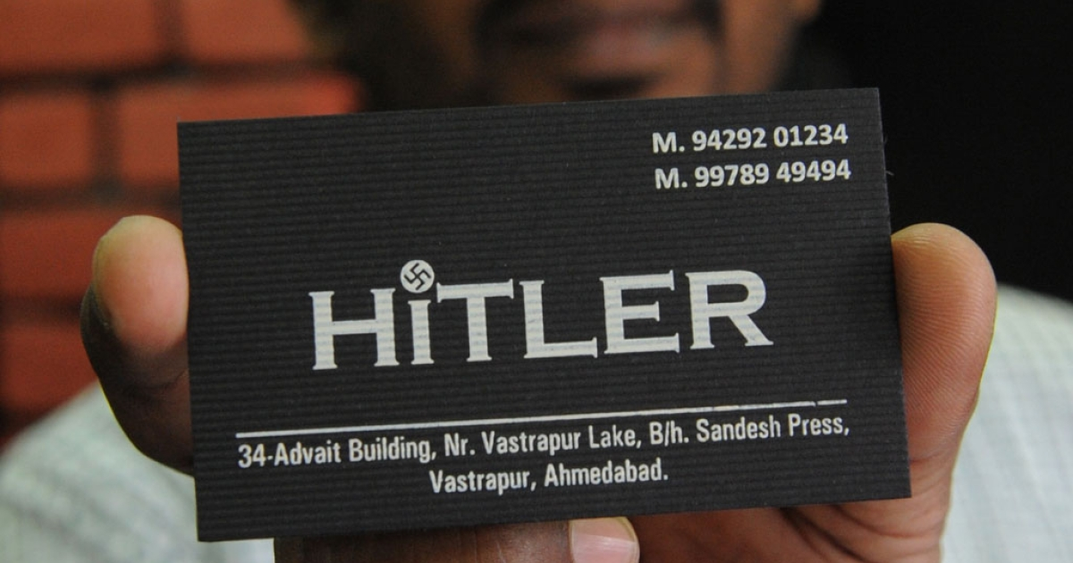 One of the two Indian owners of the 'Hitler' clothing store - Rajesh Shah - poses with a card at his shop in Ahmedabad on August 28, 2012.  Members of the Jewish community in the western Indian state have urged the shop owners to change the name of the store, which was opened on August 19, 2012. Prior to this a banner with the wording
