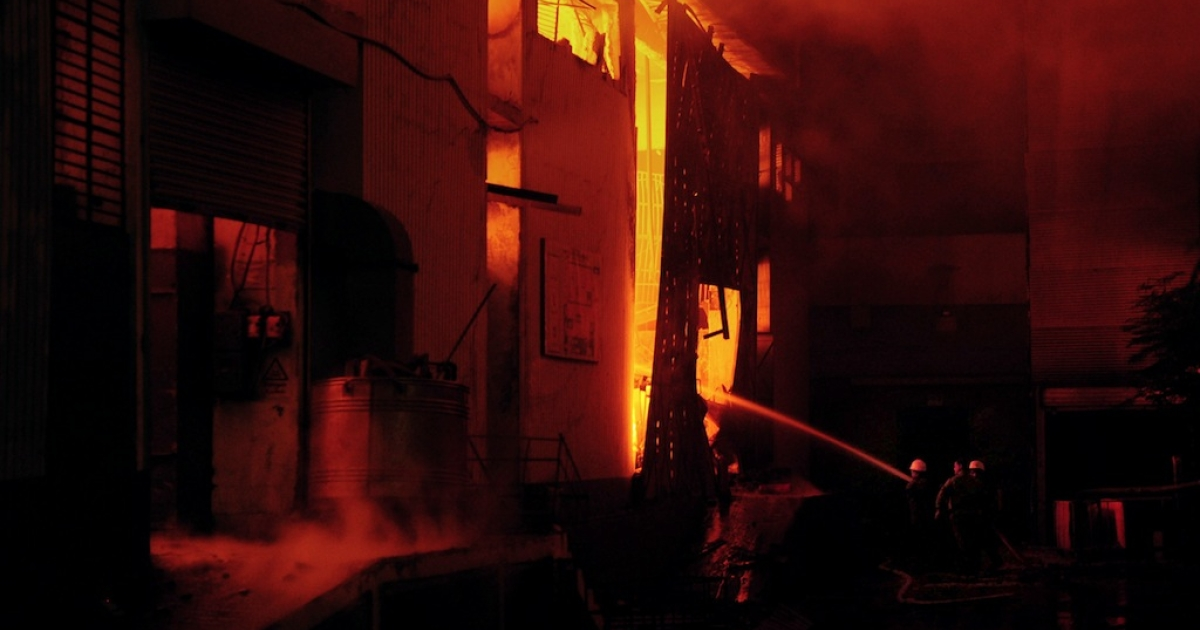 Pakistani firefighters extinguish a fire that erupted in a garment factory in Karachi on September 11, 2012.</p>