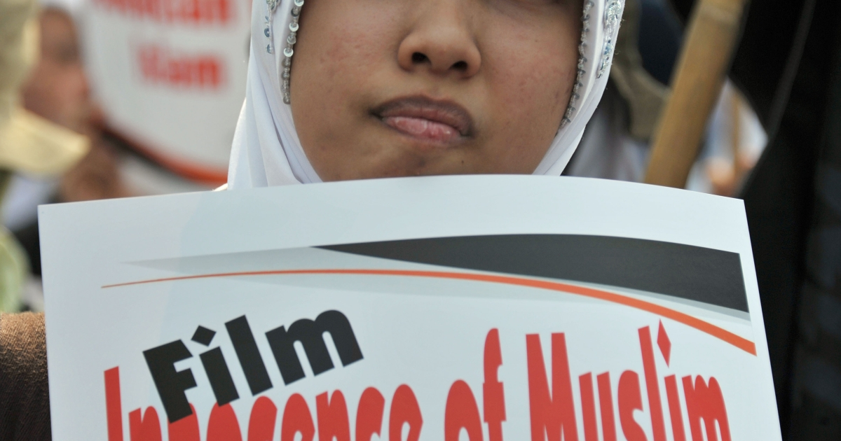 A demonstrator holds a placard during a protest against the film 'Innocence of Muslims' in Jakarta, on September 14, 2012. More than 350 Muslim fundamentalists and their supporters staged an anti-US demonstration in Jakarta Friday, spewing anger at America over an anti-Islam film</p>