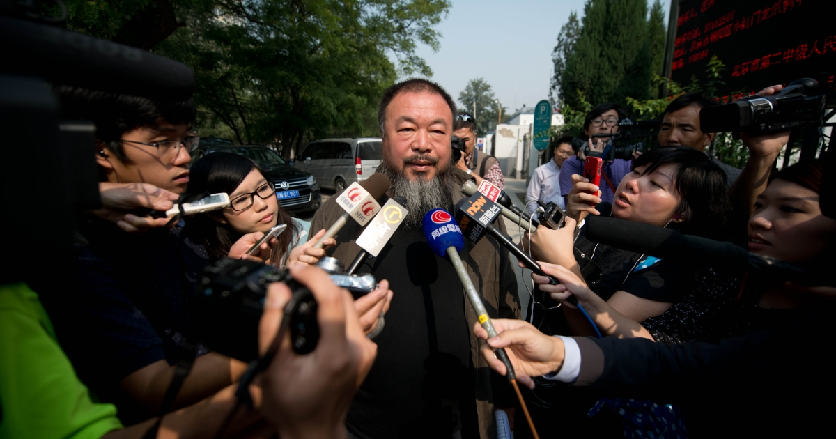 Chinese artist Ai Weiwei (C) talks to the foreign media outside a court in Beijing on September 27, 2012.</p>