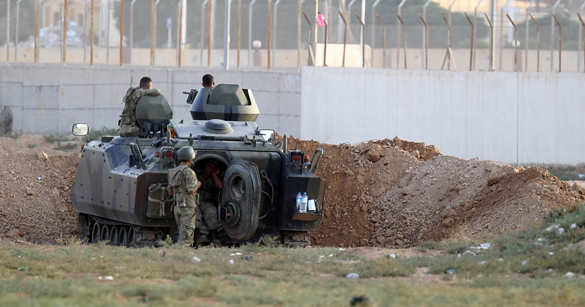 A Turkish army armoured personnel carrier is dug in on the border with Syria near Akcakale on October 7, 2012.</p>