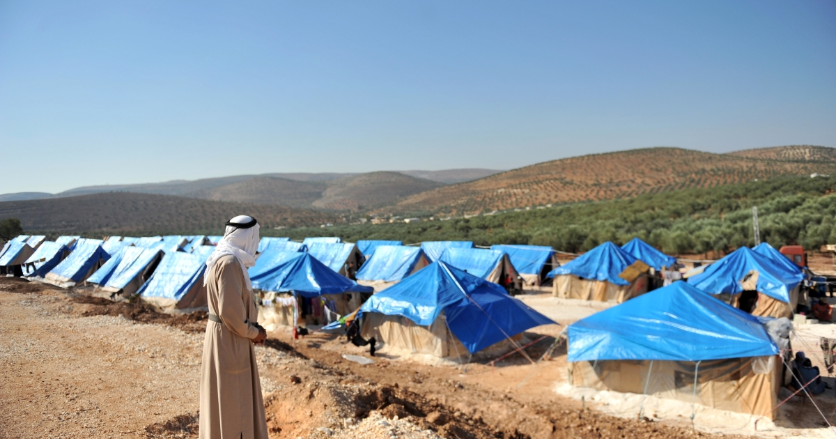 A Syrian man looks at the tents of the new refugee camp at the village of Qah, northwestern Idlib, near the Turkish border, on October 14, 2012.</p>