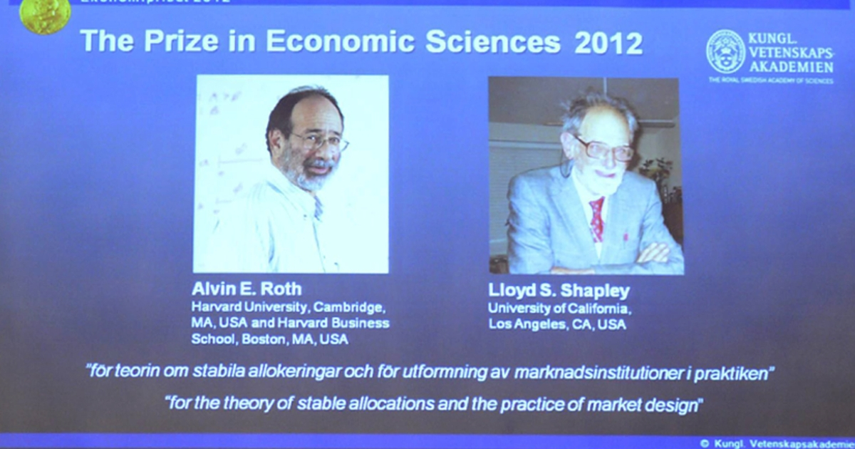 A screen displays photos of the winners of the Nobel prize in Economic Sciences US Alvin Roth (L) and Lloyd Shapley on October 15, 2012 in Stockholm during the press conference of the Royal Swedish Academy of Sciences.</p>