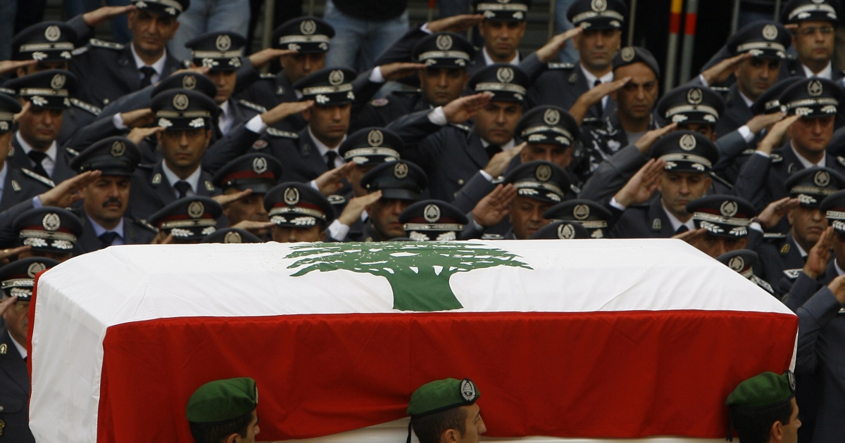 Lebanese officers from the Internal Security Forces salute as the coffin of assassinated intelligence chief General Wissam al-Hassan passes Martyrs' square, Beirut, Oct. 21, 2012. (Stringer /AFP/Getty Images).</p>