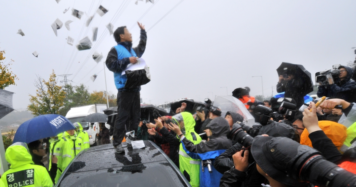 Park Sang-Hak (C), an activist and former defector from North Korea, scatters anti-Pyongyang leaflets as police block his planned rally near the tense border on a roadway in Paju, north of Seoul, on October 22, 2012.</p>