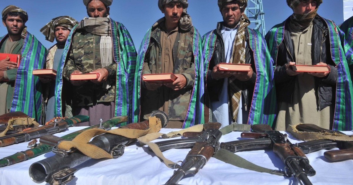 Former Taliban fighters display their weapons after they joined Afghan government forces during a ceremony in Herat on October 22, 2012.</p>