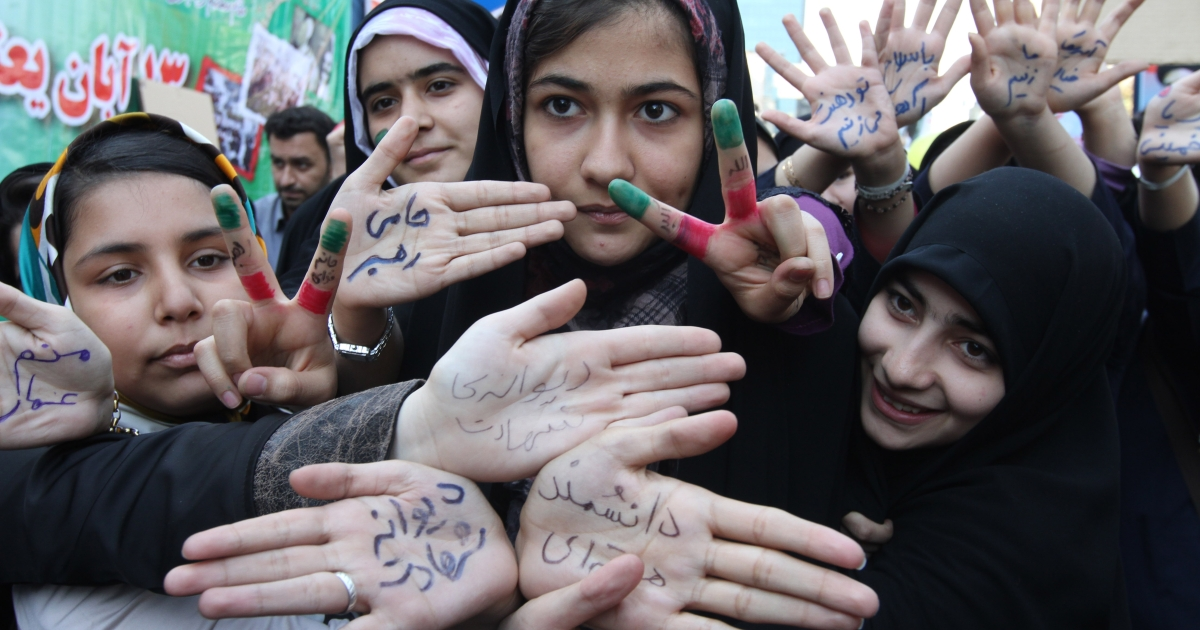 Iranian students show their palms which read in Persian,