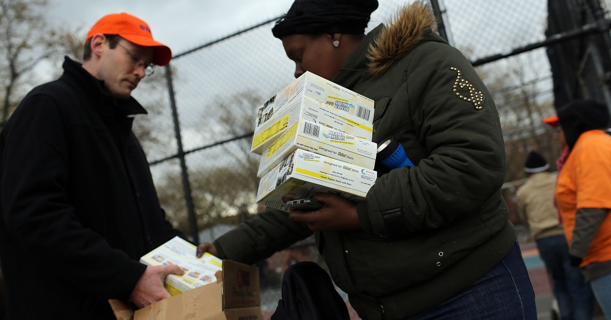 A woman recieves donated water and ready-to-eat meals at the Red Hook Houses project in Brooklyn where there is currently limited water and electricity due to Hurricane Sandy on November 2, 2012 in the Brooklyn borough of New York City.</p>