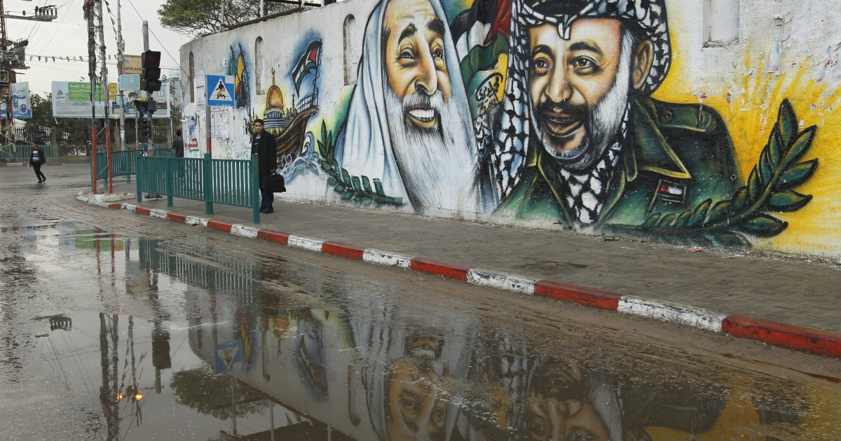 A Palestinian youth stands along a side walk with a mural behind him depicting the late Palestinian leader Yasser Arafat (R) and the late Hamas spiritual leader Sheikh Ahmed Yassin in Gaza City on November 11, 2012, as Palestinians commemorate the eighth anniversary of Arafat's death.</p>