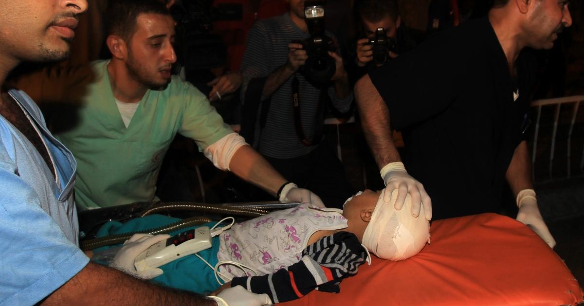 Palestinian medics wheel a wounded boy into the al-shifa hospital in Gaza City following an Israeli air strike on November 14, 2012.</p>