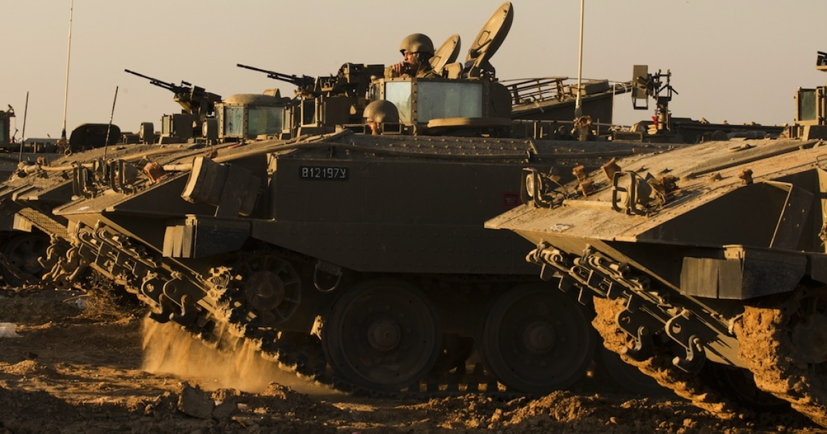 Israeli soldiers rest by their armoured personnel carriers (APC) stationned on the Israel-Gaza border on November 15, 2012. Israel will take 'whatever action is necessary' to defend its citizens from Palestinian rocket attacks, Prime Minister Benjamin Netanyahu said as the military pressed a massive operation in Gaza.</p>