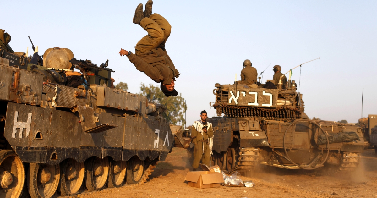 An Israeli soldier jumps from a tank in a deployment area as the conflict between Palestine and Gaza enters its seventh day on November 20, 2012 on Israel's border with the Gaza Strip.</p>