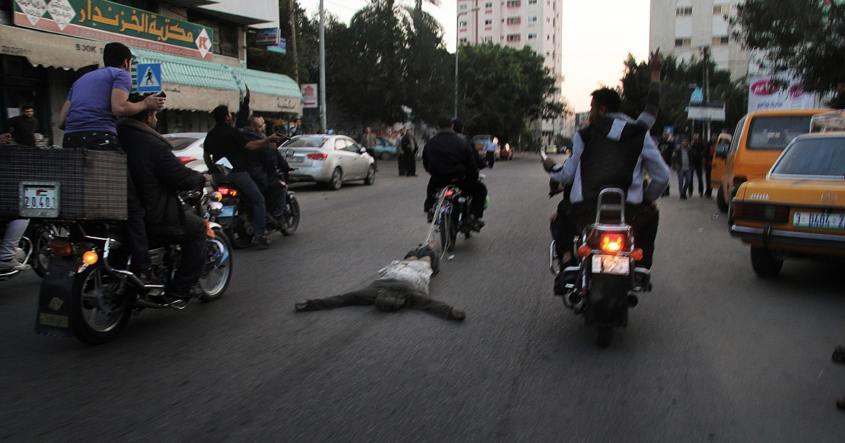 Palestinian men on a motorcycle drag the body of a man who was killed for allegedly collaborating with Israel, in Gaza City, on November 20, 2012.</p>