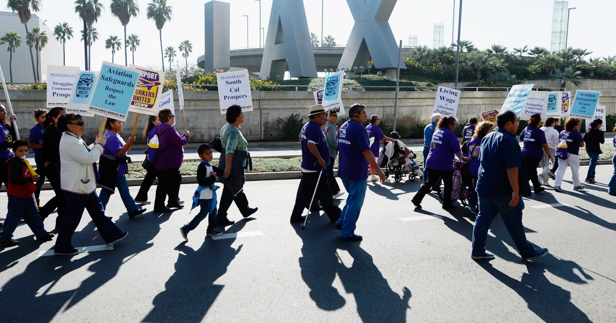 Service employees and members from several other unions march on the main thoroughfare to the entrance of Los Angeles International Airport during a large protest a day before Thanksgiving on the busiest travel day of the year November 21, 2012 in Los Angeles, California.</p>