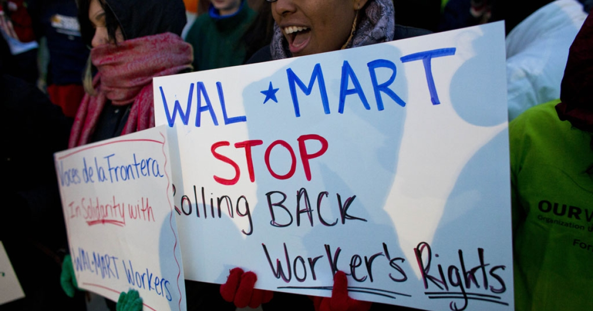 Workers and supporters march outside a local Walmart on November 23, 2012, in Milwaukee, Wisconsin. The protesters were calling for better wages and working conditions for the employees.</p>
