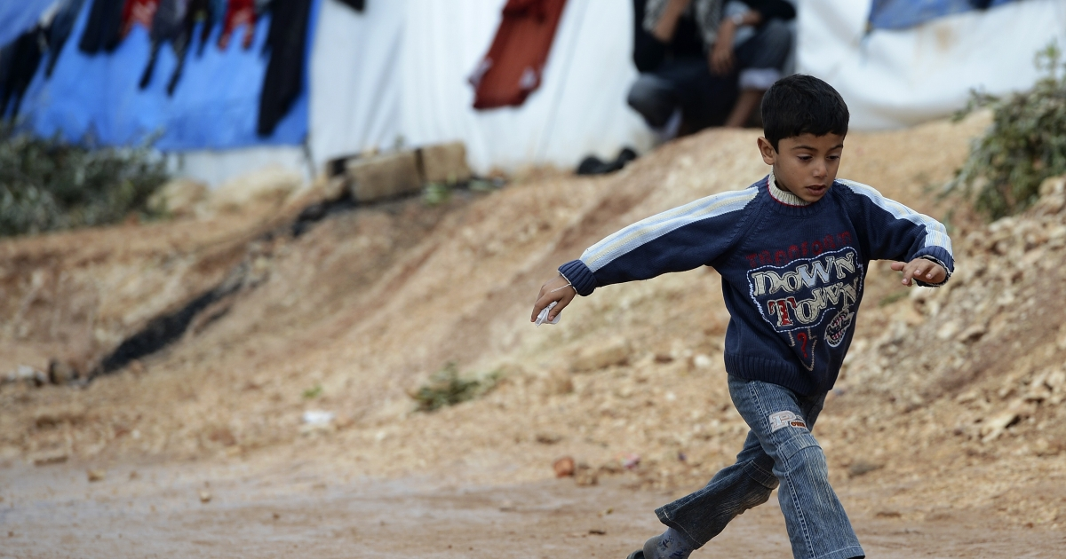 A Syrian boy jumps over a pot hole on a refugee camp in Qah, near the northwestern Syria city of Idlib on November 24, 2012.</p>