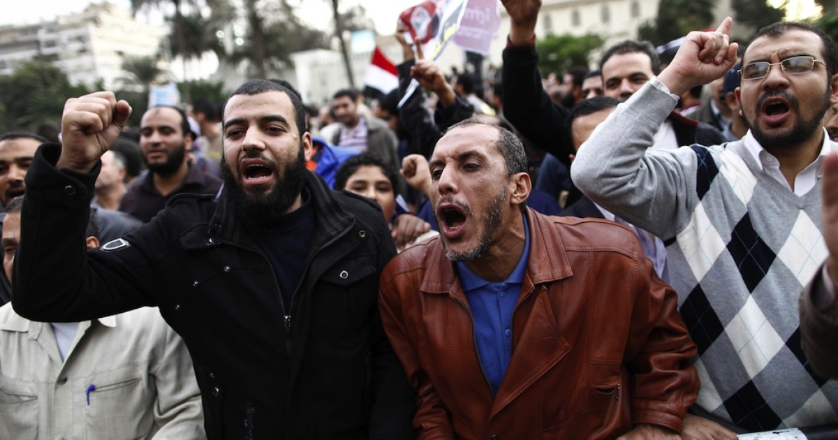 Demonstrators shout slogans outside the Egyptian presidential palace in Cairo on December 5, 2012. Three of Egyptian President Mohamed Morsi's advisers have resigned, state media said, as clashes raged outside the presidential palace over his expanded powers and a disputed draft constitution.</p>