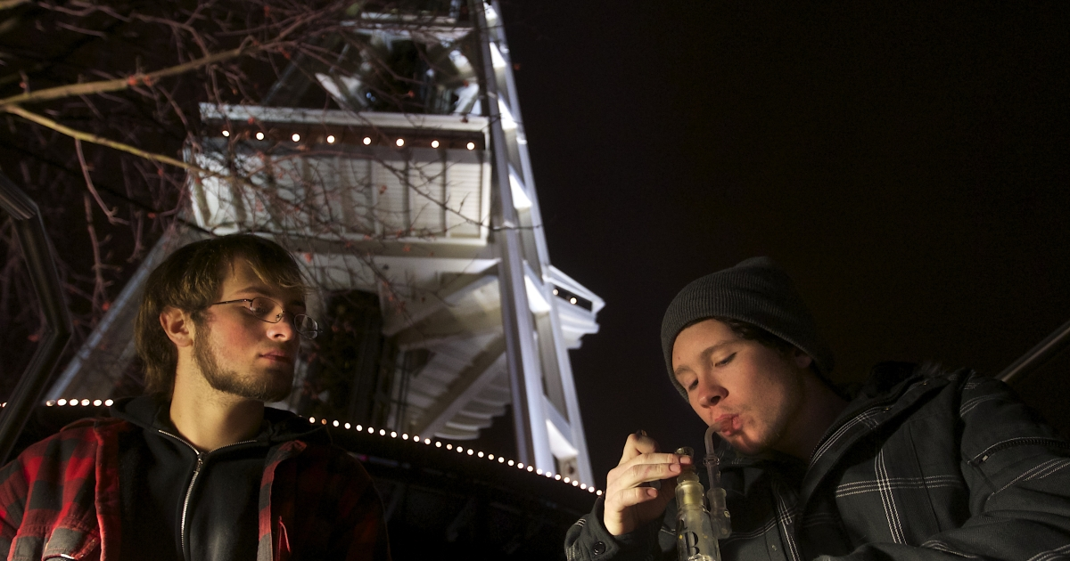 Dustin, left, and Paul of Tacoma, Washington, both of which declined to give their last names, share a water pip underneath the Space Needle shortly after a law legalizing the recreational use of marijuana took effect on December 6, 2012 in Seattle, Washington.</p>