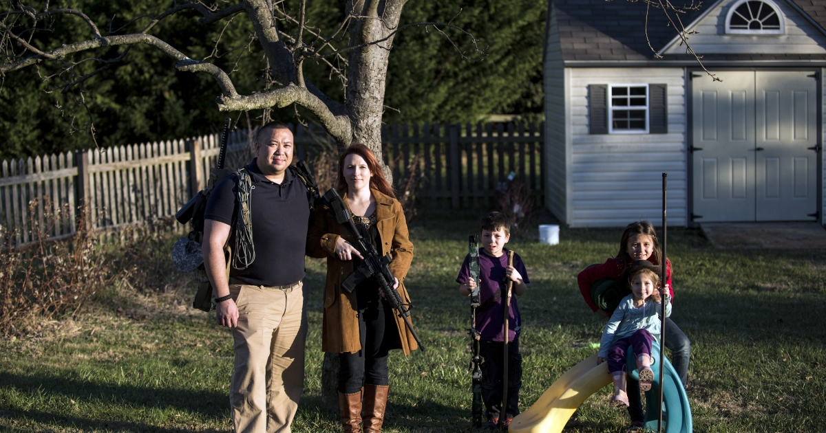 Jay Blevins and his wife Holly Blevins and their children Samuel Benjamin Blevins, 7, Elliana Grace Blevins, 9, and Evangeline Joy Blevins, 4, pose beneath one of their apple trees with survival gear including a buyout bag, an AR-15 rifle and a hunting bow December 5, 2012 in Berryville, Virginia. The family has been preparing, along with a group, for a possible doomsday scenario.</p>