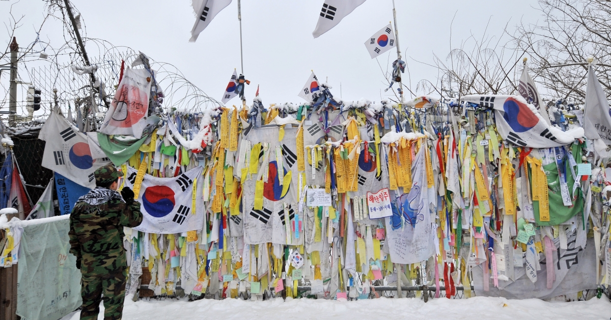 A South Korean soldier looks at 'reunification ribbons' displayed on a military barbed wire fence at Imjingak peace park in Paju near the Demilitarized Zone (DMZ) dividing the two Koreas on January 1, 2013.</p>