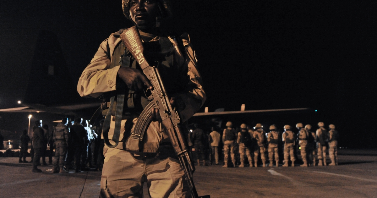 A soldier stands guard as Nigerian troops arrive at the airport in Bamako on January 17, 2013.</p>