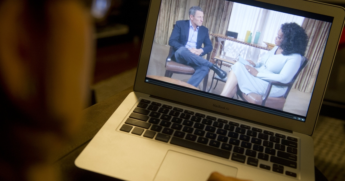 A woman watches on her computer as Oprah Winfrey interviews cyclist Lance Armstrong about doping while competing professionally in the sport, as seen from Washington, DC, on January 17, 2013.</p>