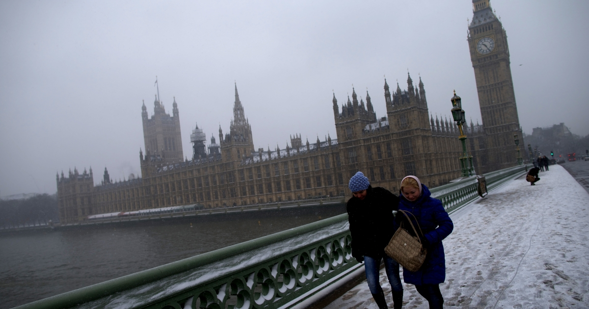 People walk across Westminster Bridge during snowfall in central London on January 20, 2013. Passengers were forced to sleep on the floor at London's Heathrow Airport overnight, media said, after heavy snow grounded hundreds of flights and left thousands of people stranded.</p>