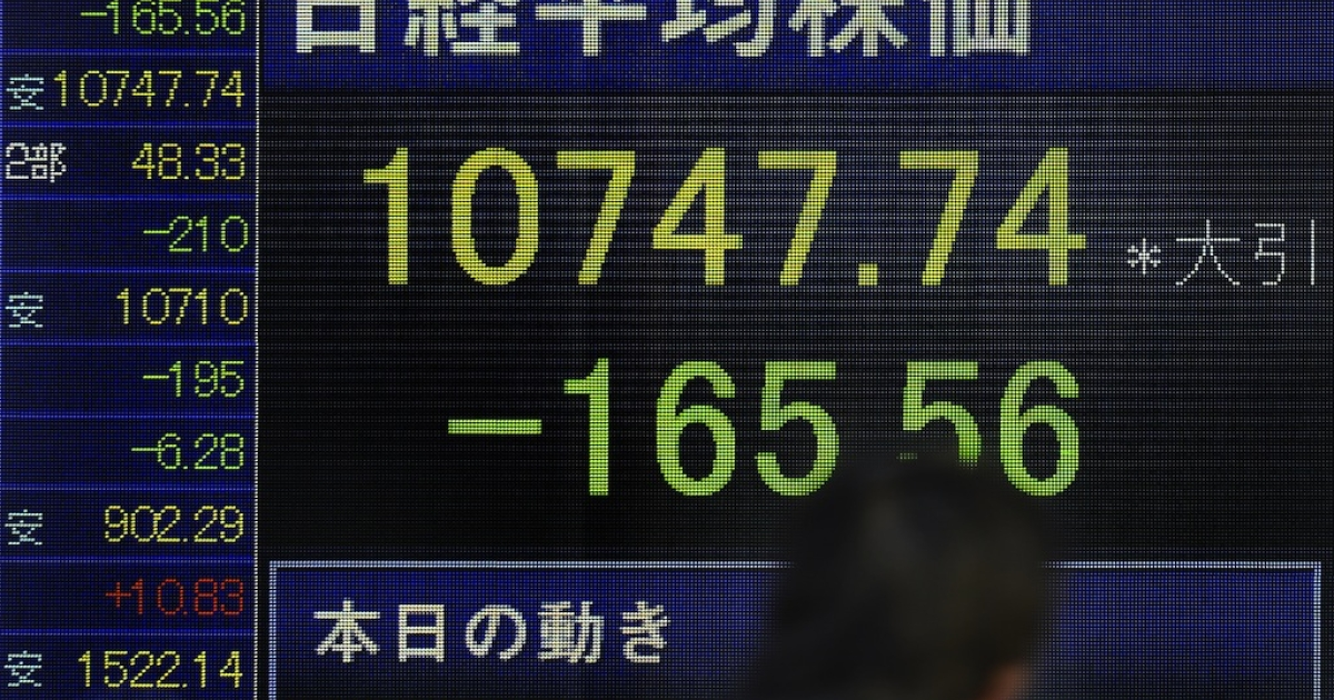 A man walks past an electronic quotation board flashing the Nikkei key index of the Tokyo Stock Exchange (TSE) in front of a securities company in Tokyo on January 21, 2013. The Bank of Japan is set to meet to discuss fiscal and monetary policy.</p>