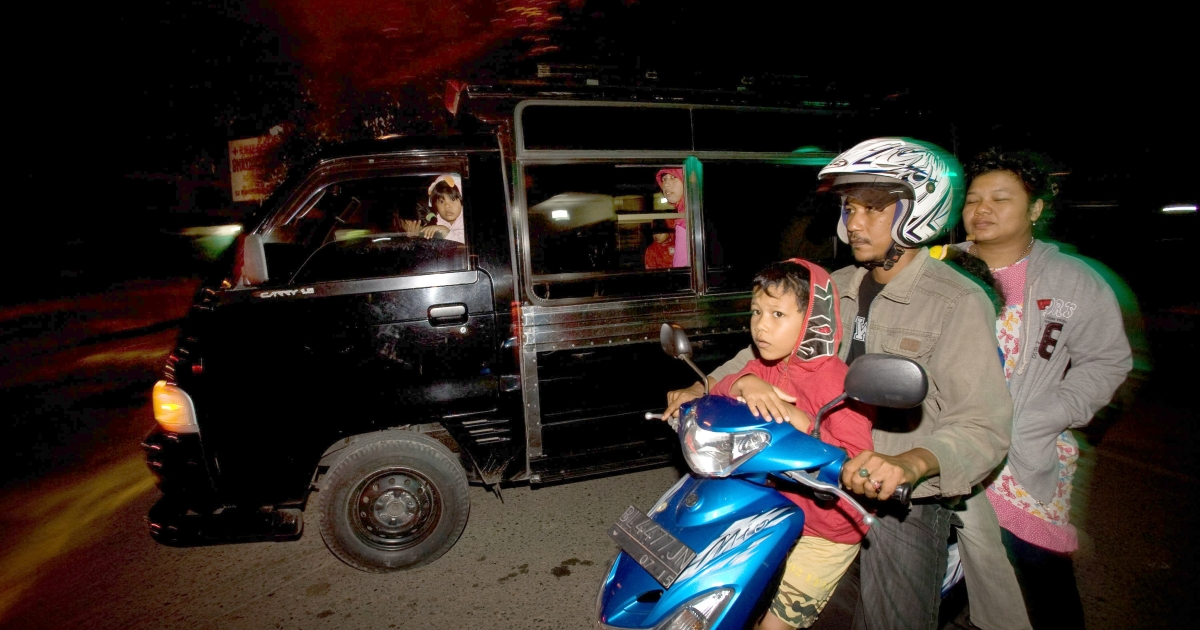 Families flee on motorcycles and cars to higher grounds in the capital Banda Aceh following an earthquake that struck off Indonesia's Aceh province early January 22, 2013, killing an 8-year old girl and injuring others.</p>