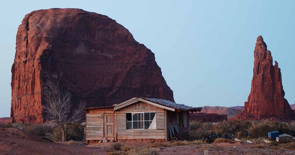 An old house stands near sandstone formations south of Rock Point December 5, 2002 on the Navajo Indian Reservation, Arizona.</p>
