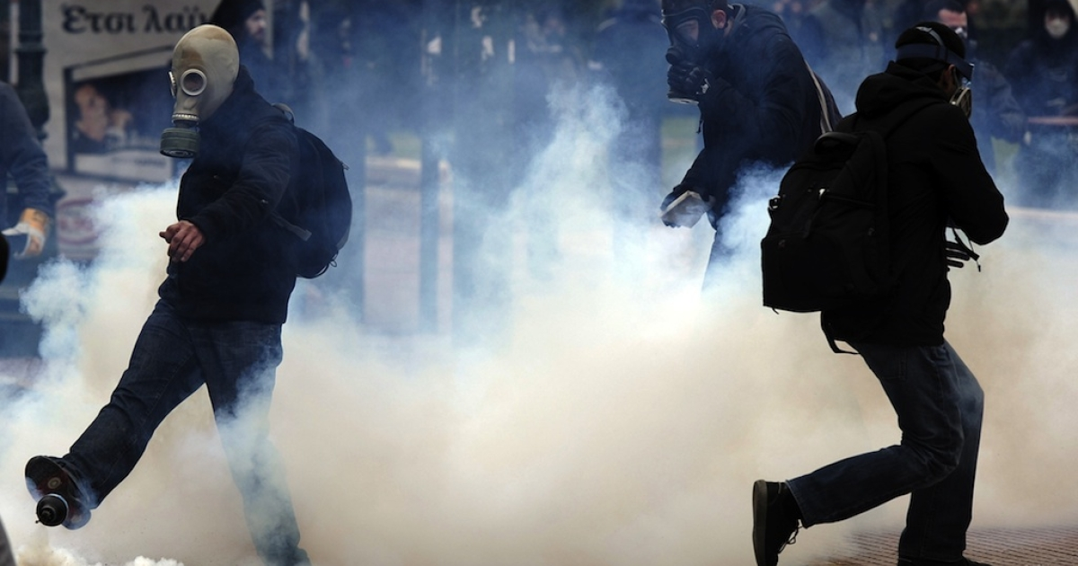 A protester kicks a tear gas canister in Athens on Feb. 10. Greek protesters threw stones and firebombs at riot police who responded with tear gas.</p>