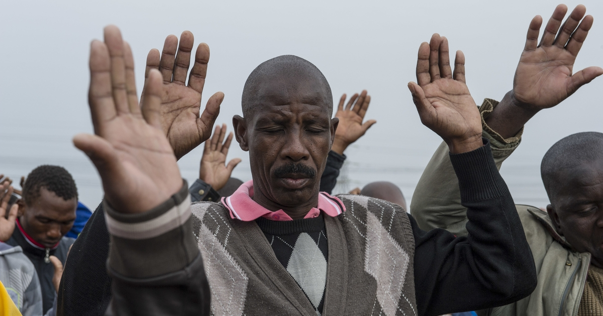 Striking Lonmin platinum miners pray at the edge of the shantytown of Nkanini in northeastern South Africa where they live. Most of the miners are still on strike, asking for a wage of12,500  rand before deductions. Thirty-four miners were killed by police and ten others including two police were killed in a clash with strikers.</p>