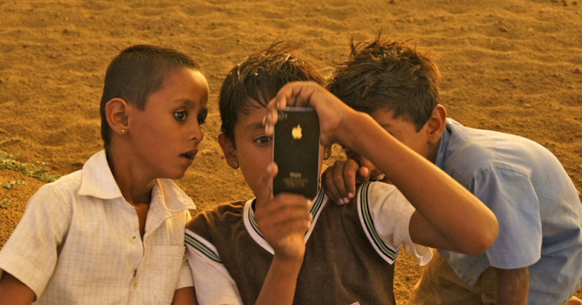 In the desert of India in the state of Rajasthan, three boys study an iphone, amazed about its reversible camera. The iphone costs more that what they need in order to live for one year.</p>