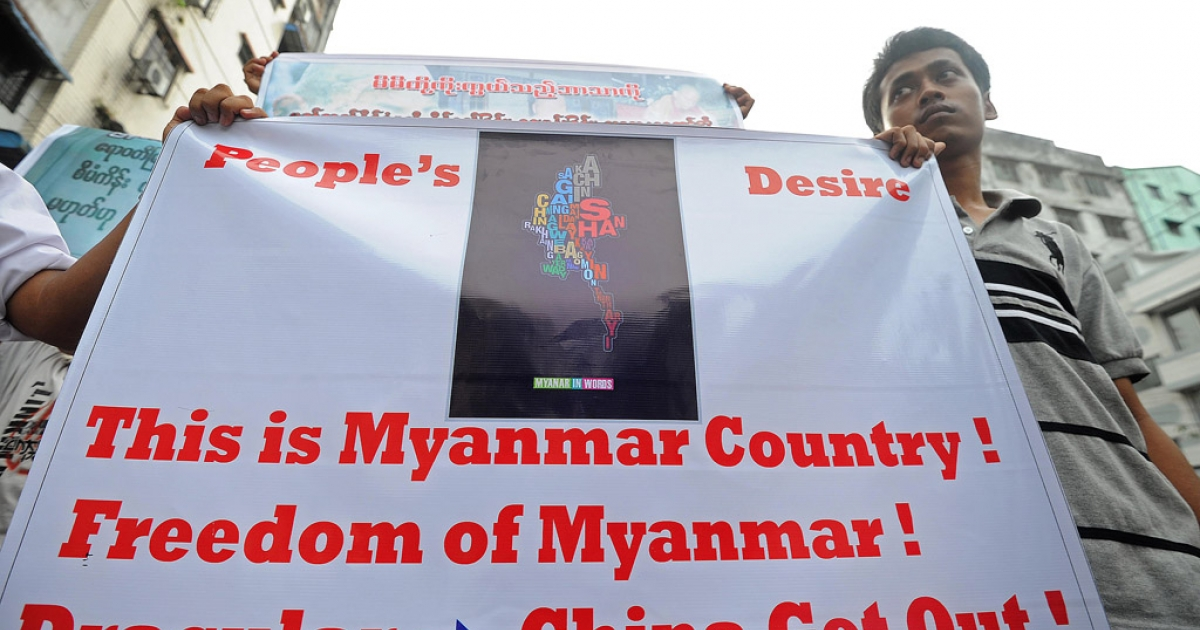 A man holds a banner during a protest in Yangon on December 2, 2012 against a Chinese-backed copper mine in Monywa in northern Myanmar.</p>