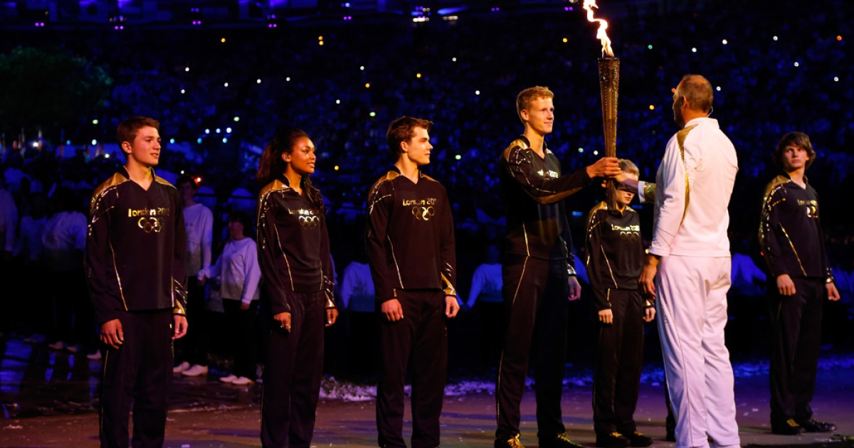 Torchbearer Sir Steve Redgrave poses with seven young torchbearers who lit the flame during the 2012 London Olympics opening ceremonies at the Olympic Stadium on July 27, 2012 in London, England.</p>