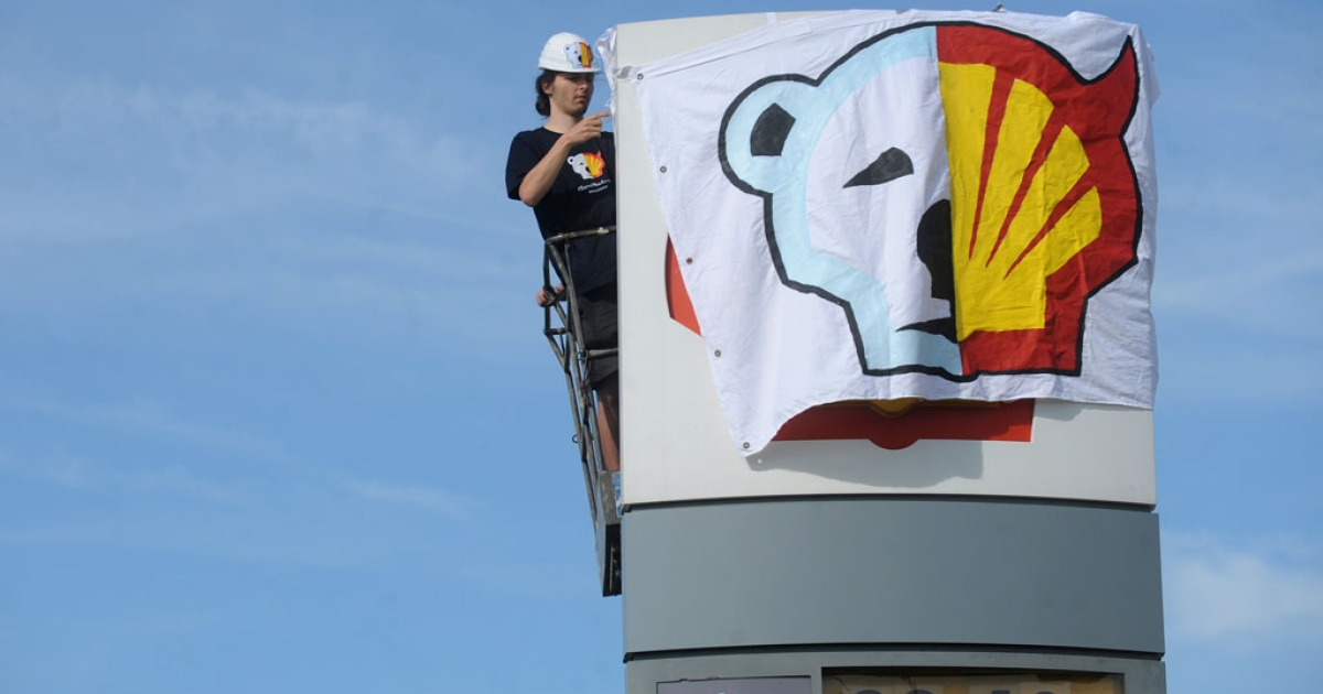 A Greenpeace activist covers the logo of the Shell oil company to protest on May 10, 2012 against the heading of the an icebreaker for Shell's Arctic oil drilling project in the north of Alaska.</p>